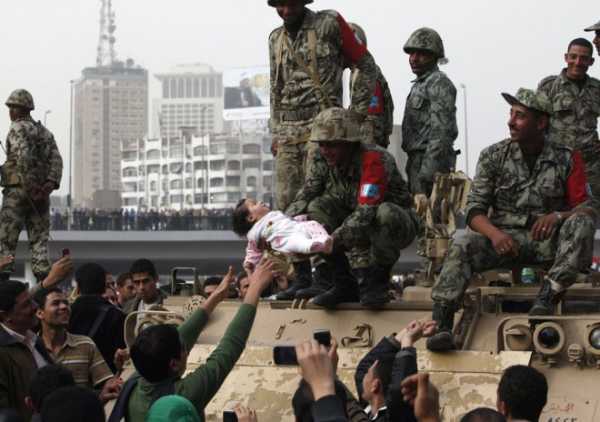 A protester reaches out as a soldier holds a child during a demonstration in Cairo